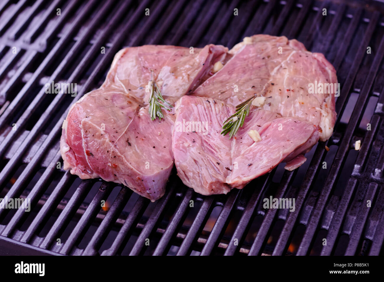 Fresh juice piece of lamb shank seasoned with green rosmary and fresh garlic, on really clean weber gas bbq - Stock Image