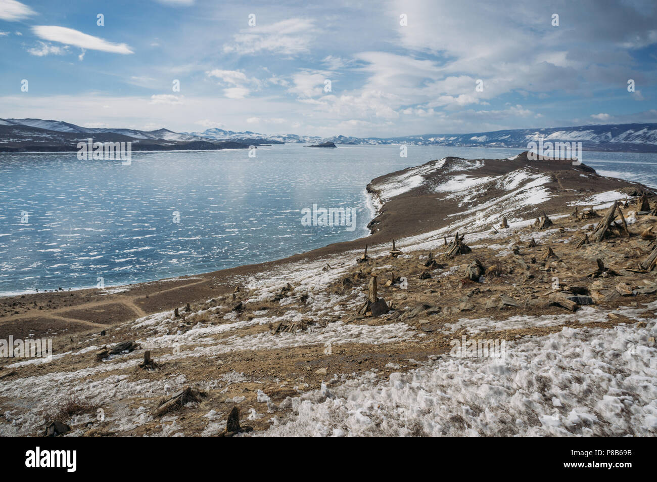 view of sandy mountain lake shore against water and hills on