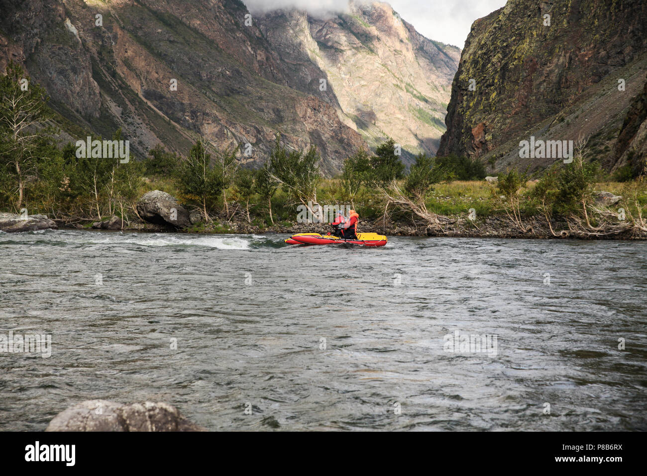 side view of people on kayaks rafting on mountain river and beautiful landscape, Altai, Russia - Stock Image