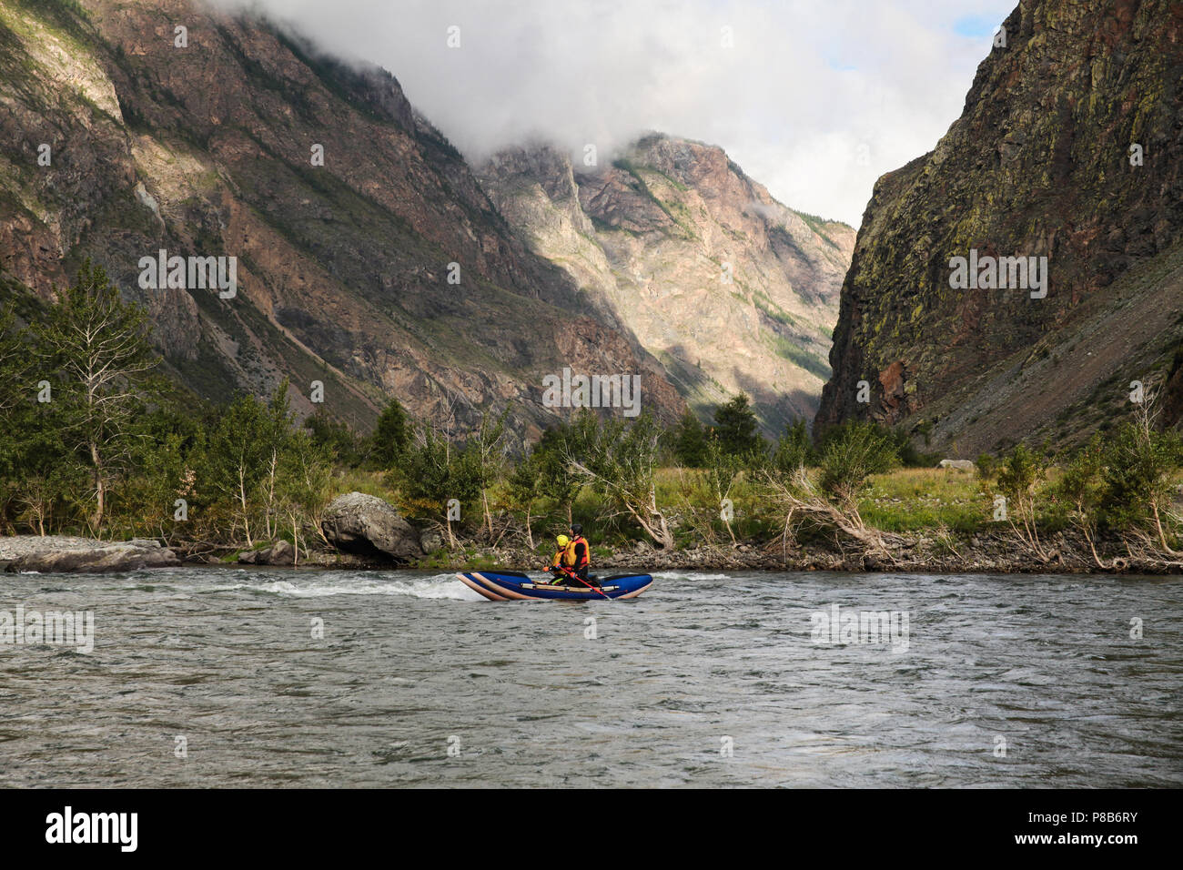 people on kayaks rafting on mountain river and beautiful landscape, Altai, Russia - Stock Image
