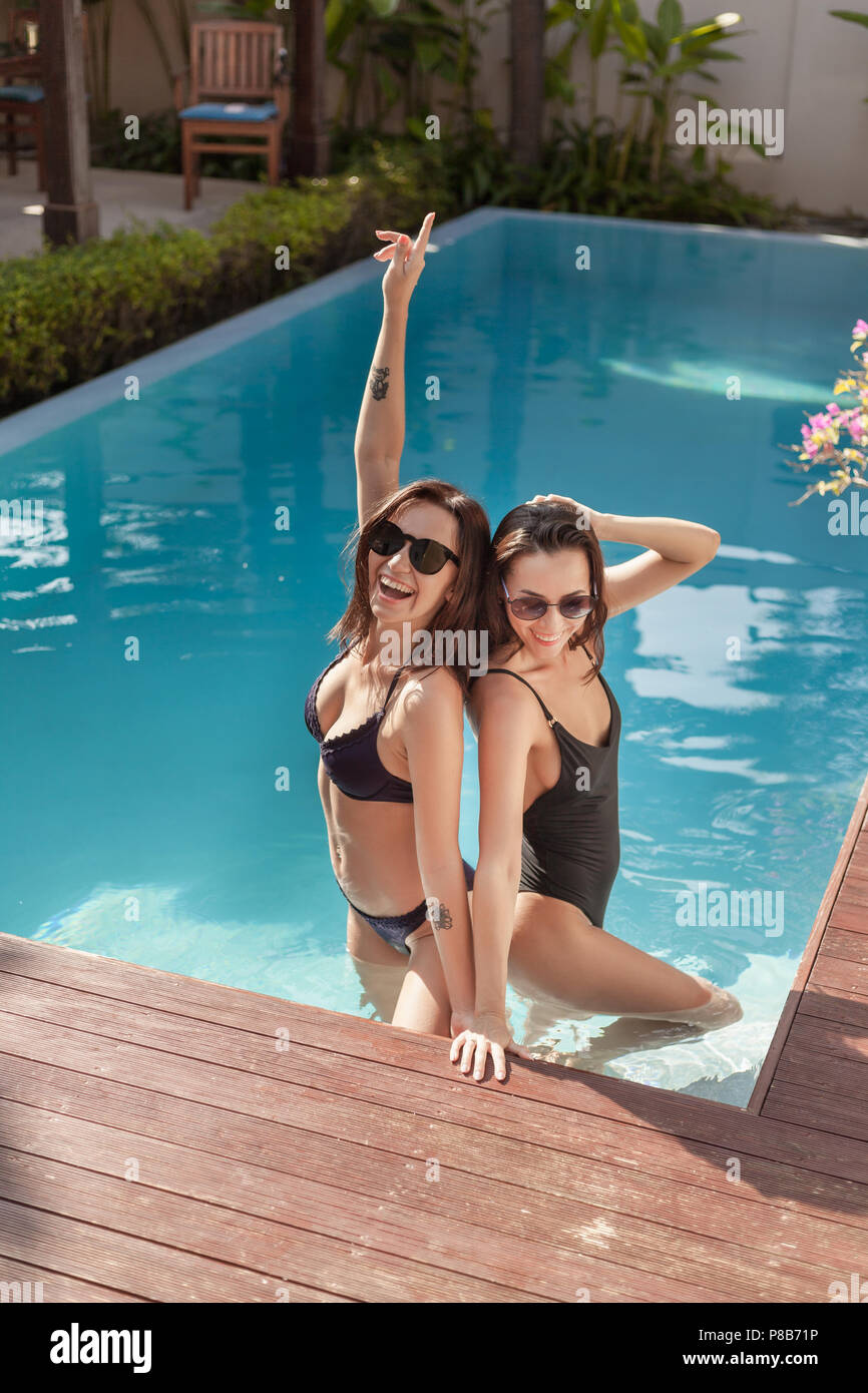 attractive young women in bikini and swimsuit at poolside - Stock Image