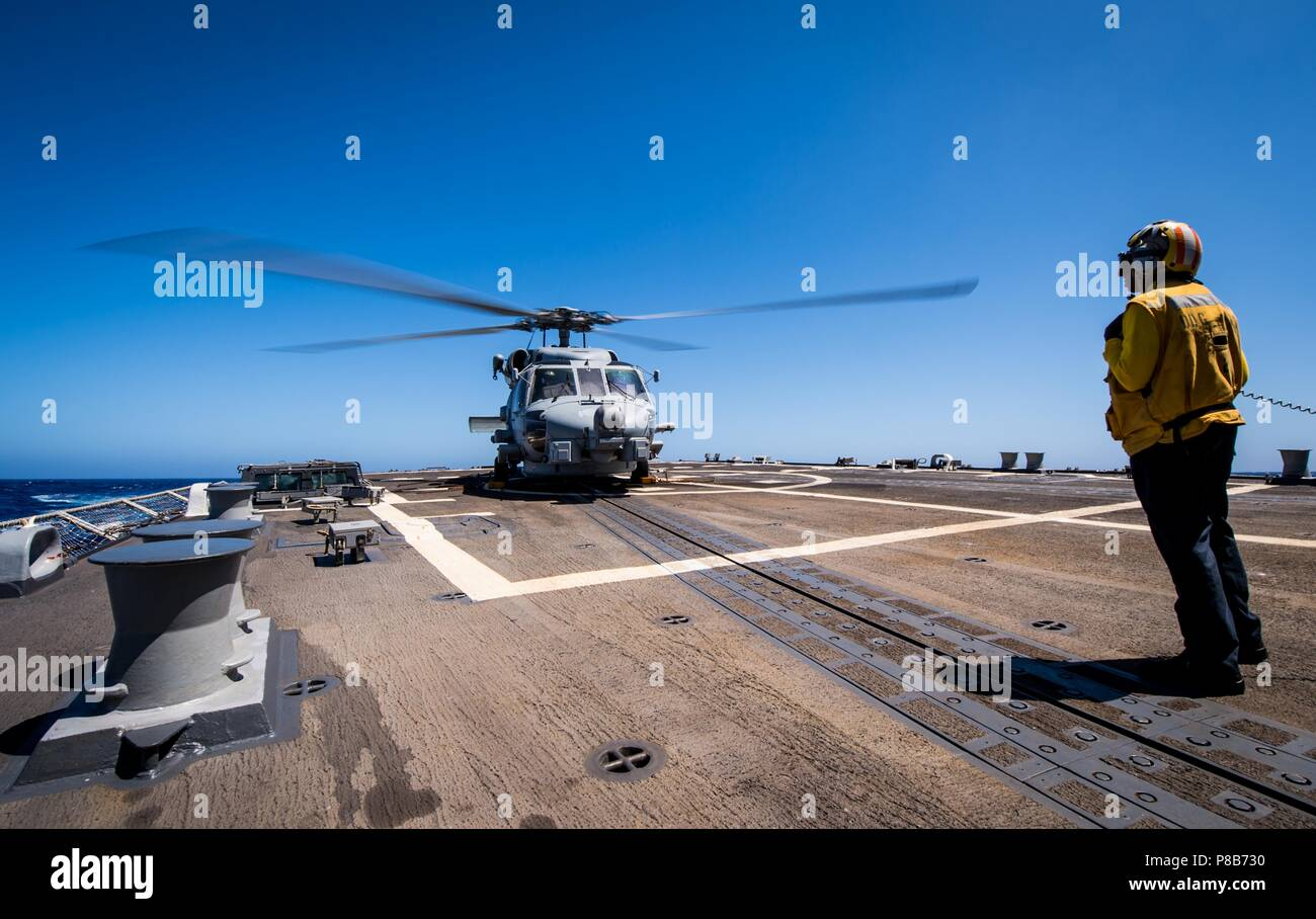 180623-N-LI768-1067 PACIFIC OCEAN (June 23, 2018) - Boatswain's Mate 3rd Class Aaliyah Terrell, assigned to the guided-missile destroyer USS Dewey (DDG 105), stands by as an MH-60R Sea Hawk helicopter assigned to the 'Magicians' of Helicopter Maritime Strike Squadron (HSM) 35, prepares for takeoff, June 23, 2018. Dewey is underway in the U.S. 3rd Fleet area of operations. (U.S. Navy photo by Mass Communication Specialist 2nd Class Devin M. Langer/Released). () - Stock Image