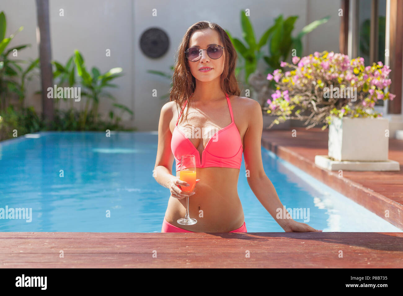 attractive young woman in bikini at poolside - Stock Image