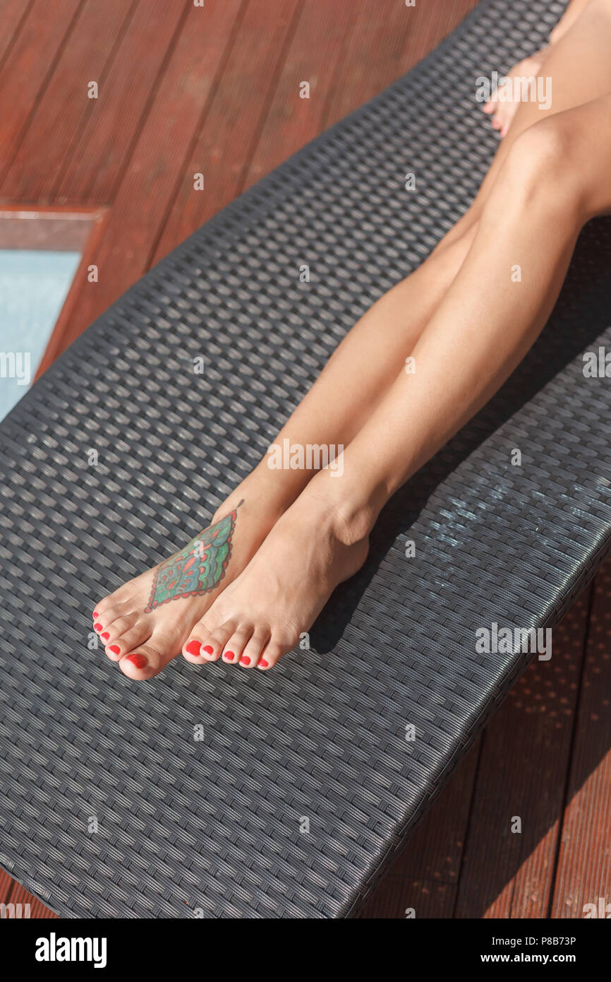 60b99ce43 cropped shot of woman with tattoo on foot relaxing on sun lounge - Stock  Image
