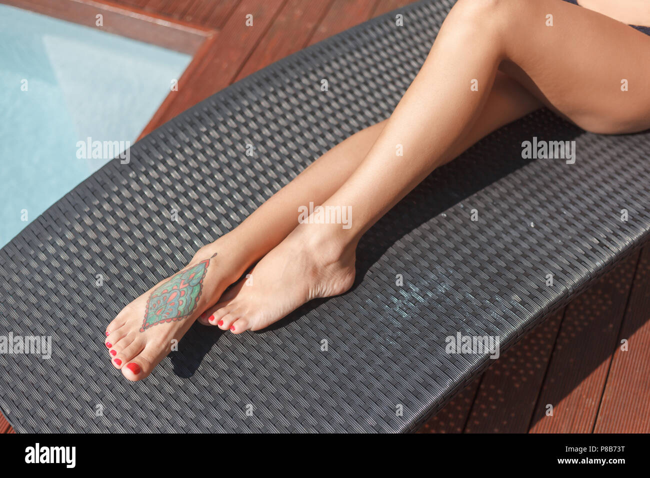 cropped shot of woman with tattoo on foot lying on sun lounge - Stock Image