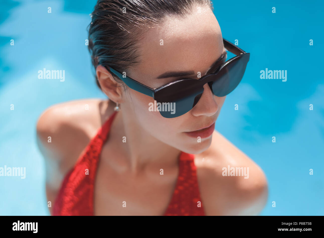 close-up portrait of young wet woman in bikini at swimming pool - Stock Image