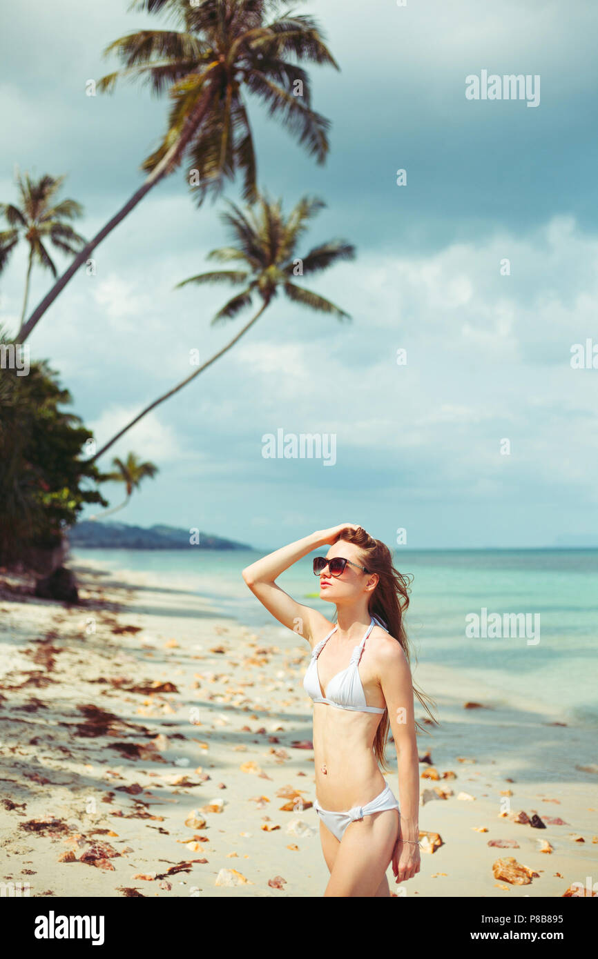 portrait of young woman in bikini and sunglasses on coastline near ocean - Stock Image