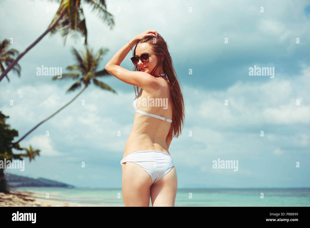 back view of smiling woman in bikini and sunglasses on beach - Stock Image