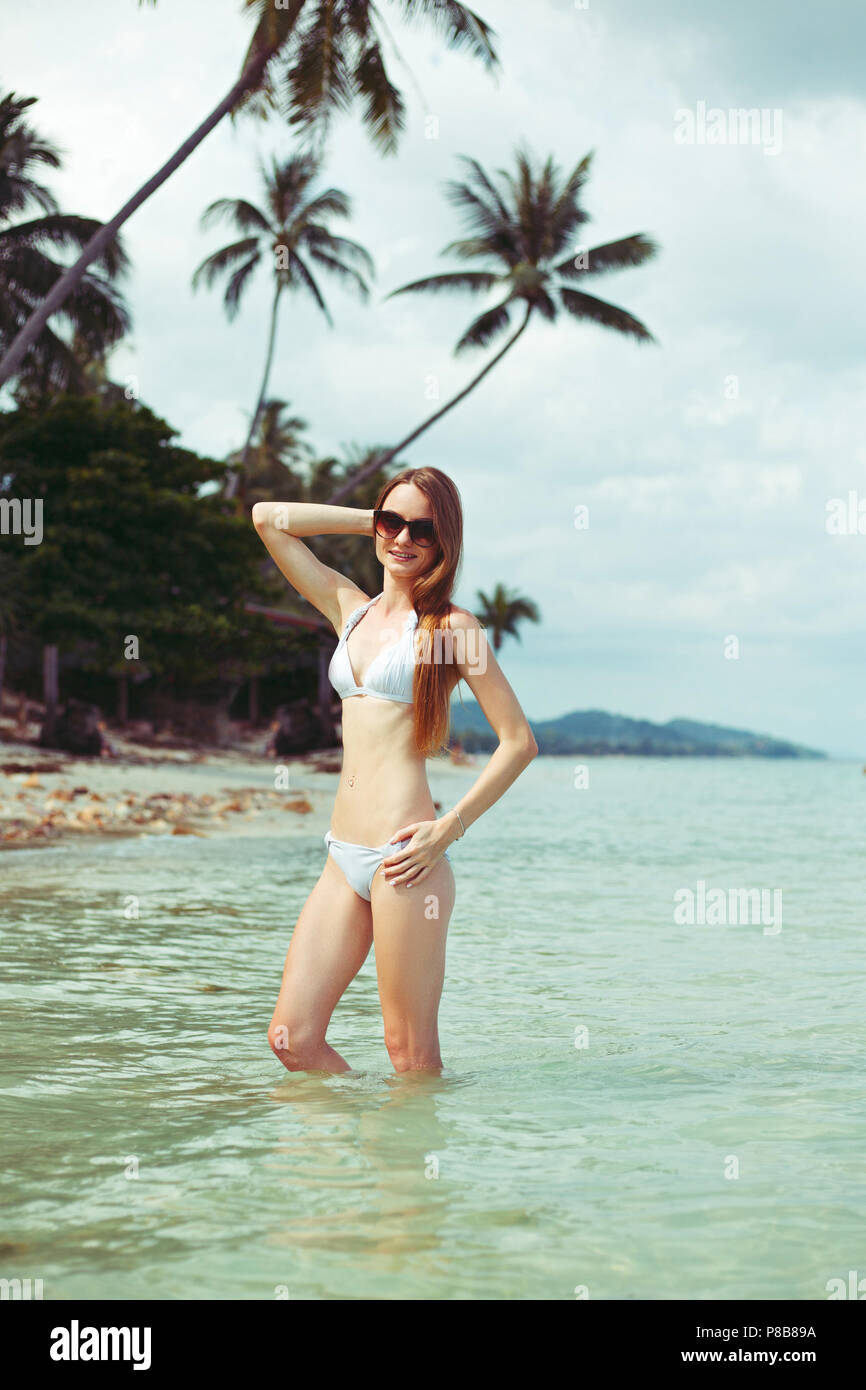 portrait of young woman in bikini and sunglasses standing in ocean - Stock Image