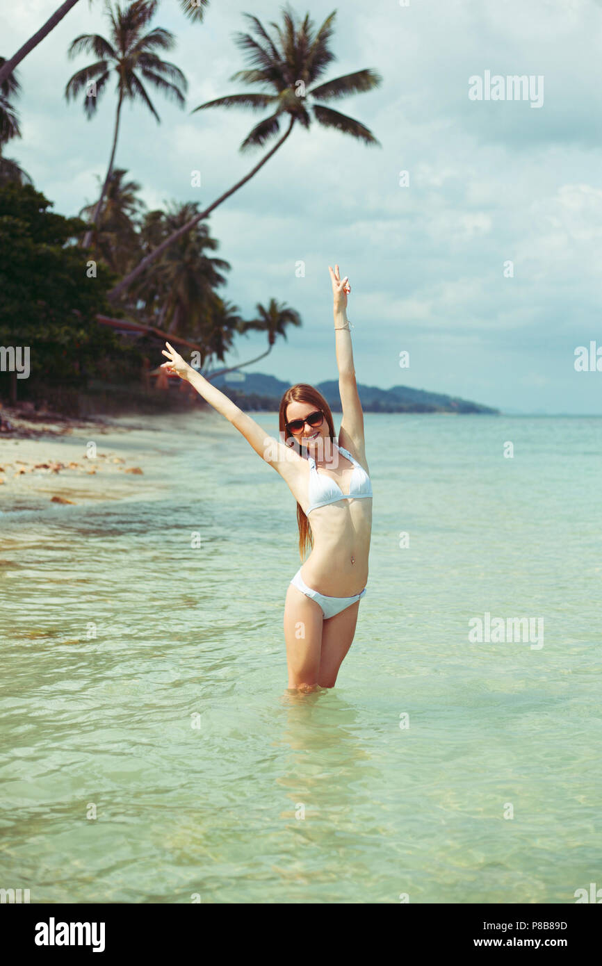 portrait of smiling woman in bikini and sunglasses with outstretched arms standing in ocean - Stock Image