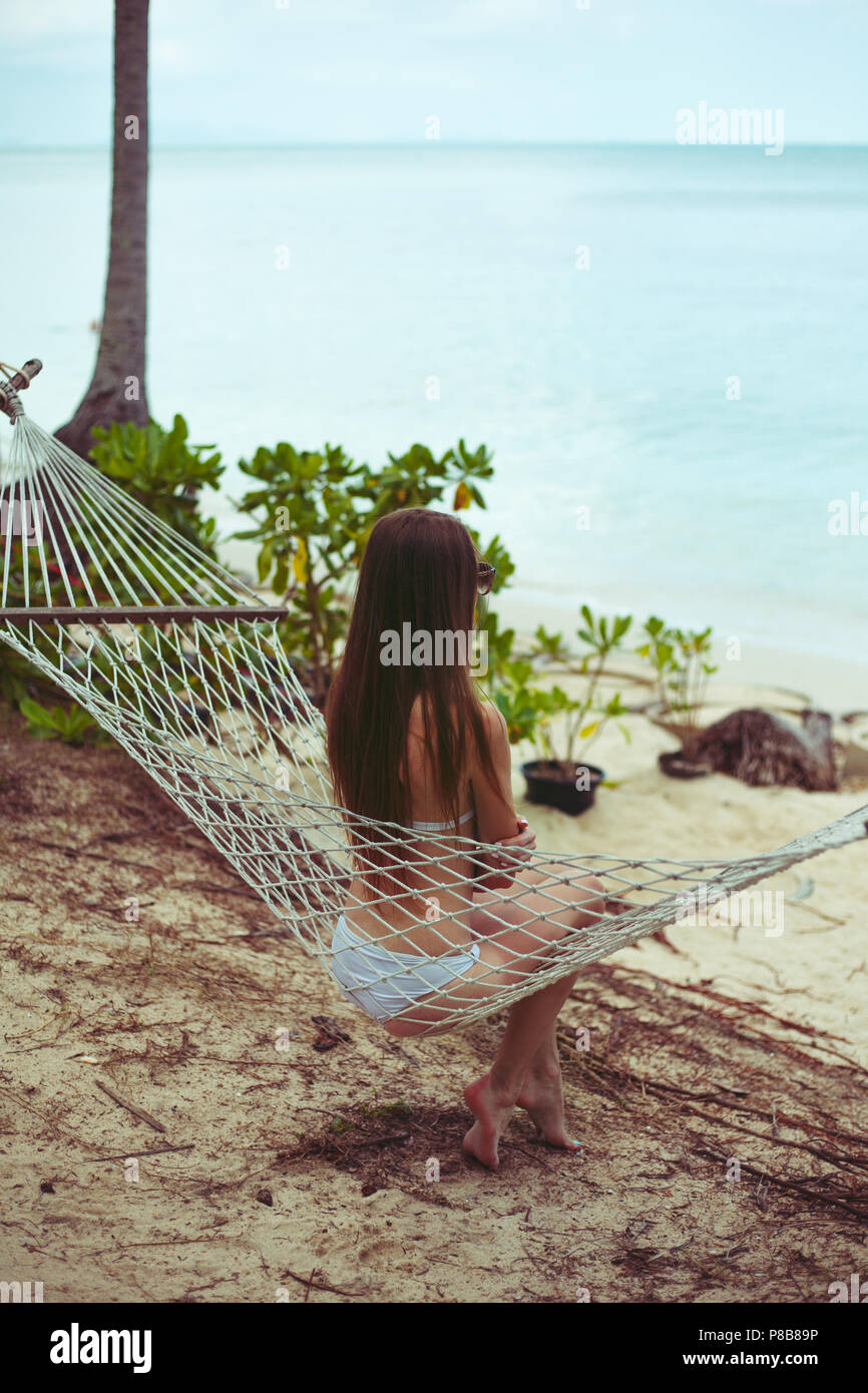 back view of woman in bikini resting in hammock with ocean on background - Stock Image