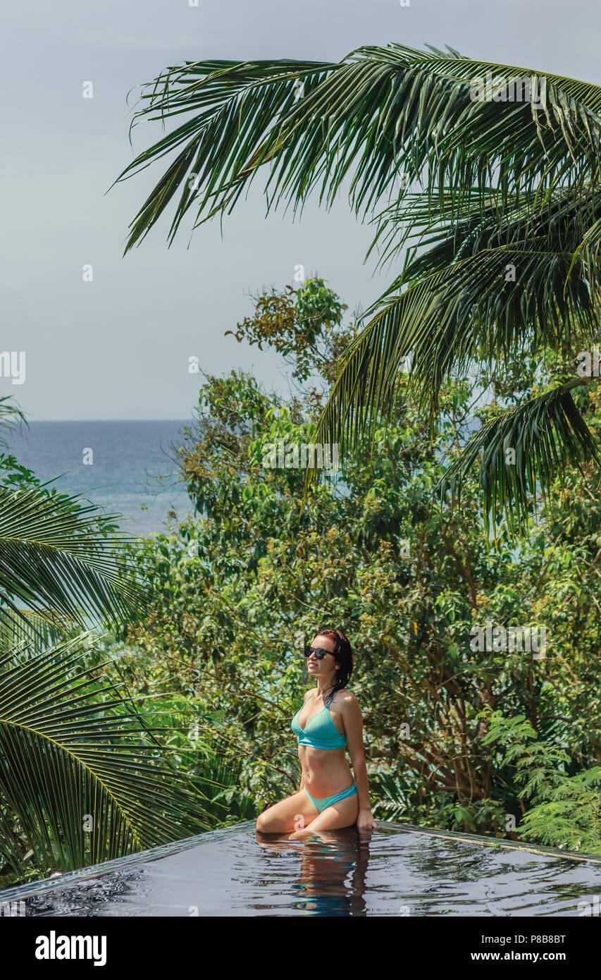 beautiful girl in bikini sitting on poolside at tropical resort - Stock Image