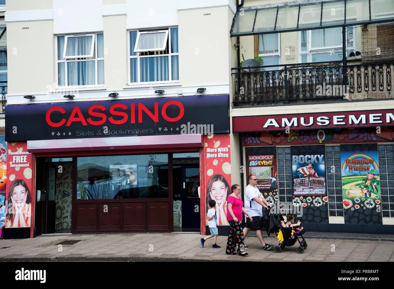 Bognor Regis, Sussex. A family walk past slot machine  amusements. - Stock Image