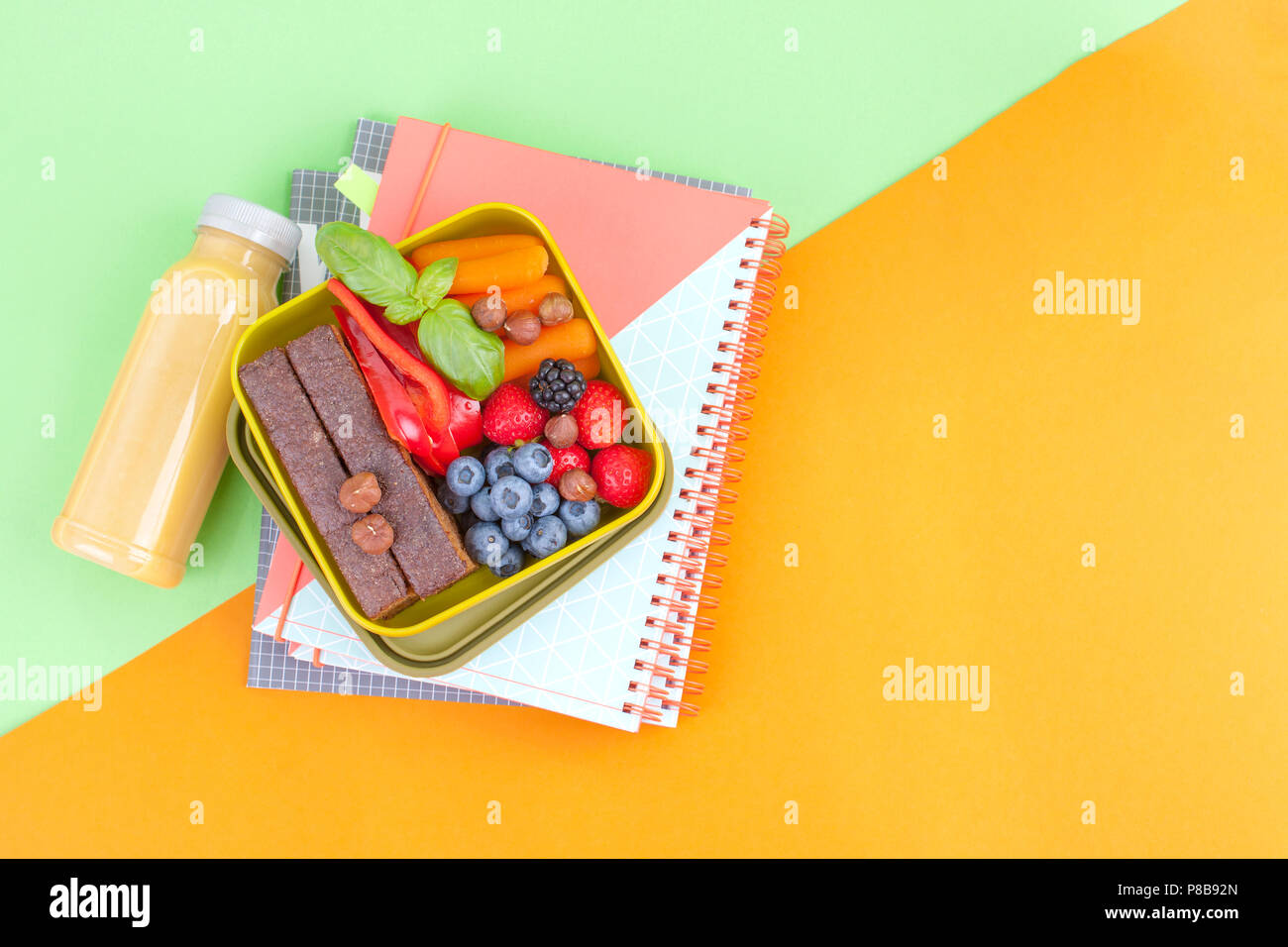 Lunch box with healthy food and juice from fresh berries. Toast and apple. books for school and green background. takeaway food. copy space. flat lay - Stock Image