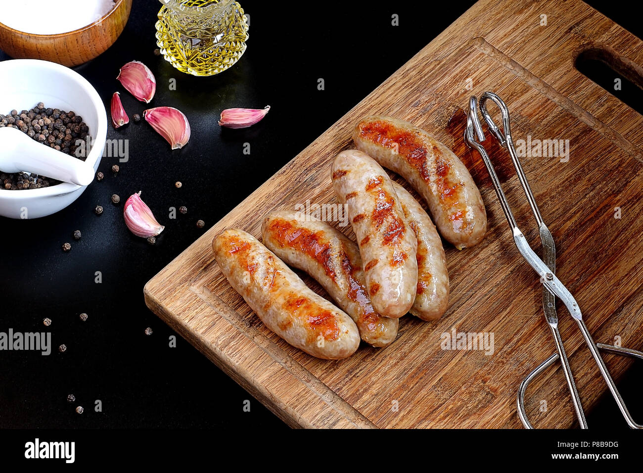 Hot Grilled German Bratwurst rest on a Wooden Board Stock Photo