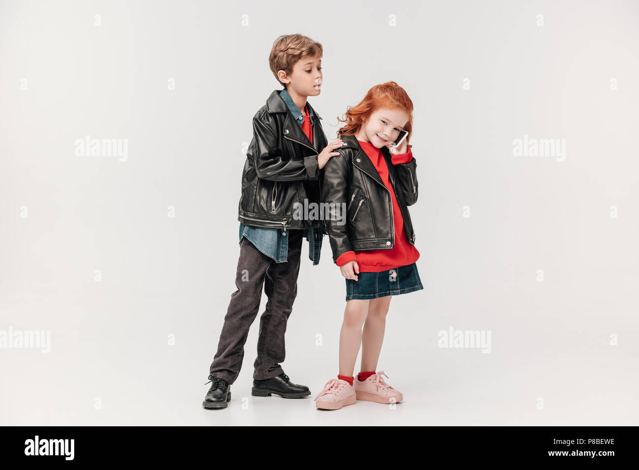 jealous little boy listening while his girl talking by phone isolated on grey - Stock Image