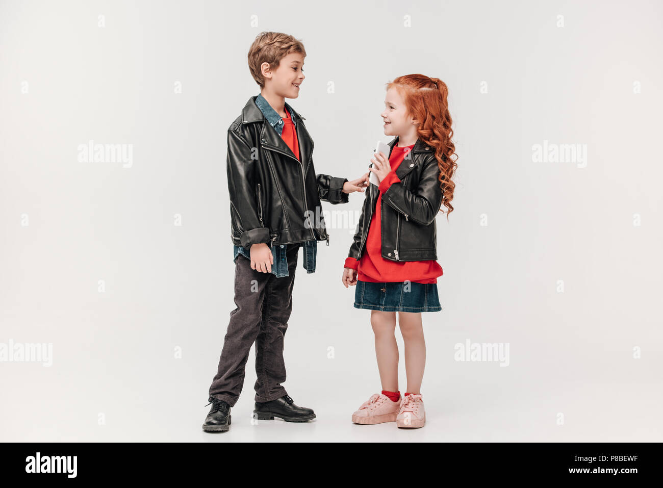 adorable stylish little kids couple with smartphone isolated on grey - Stock Image
