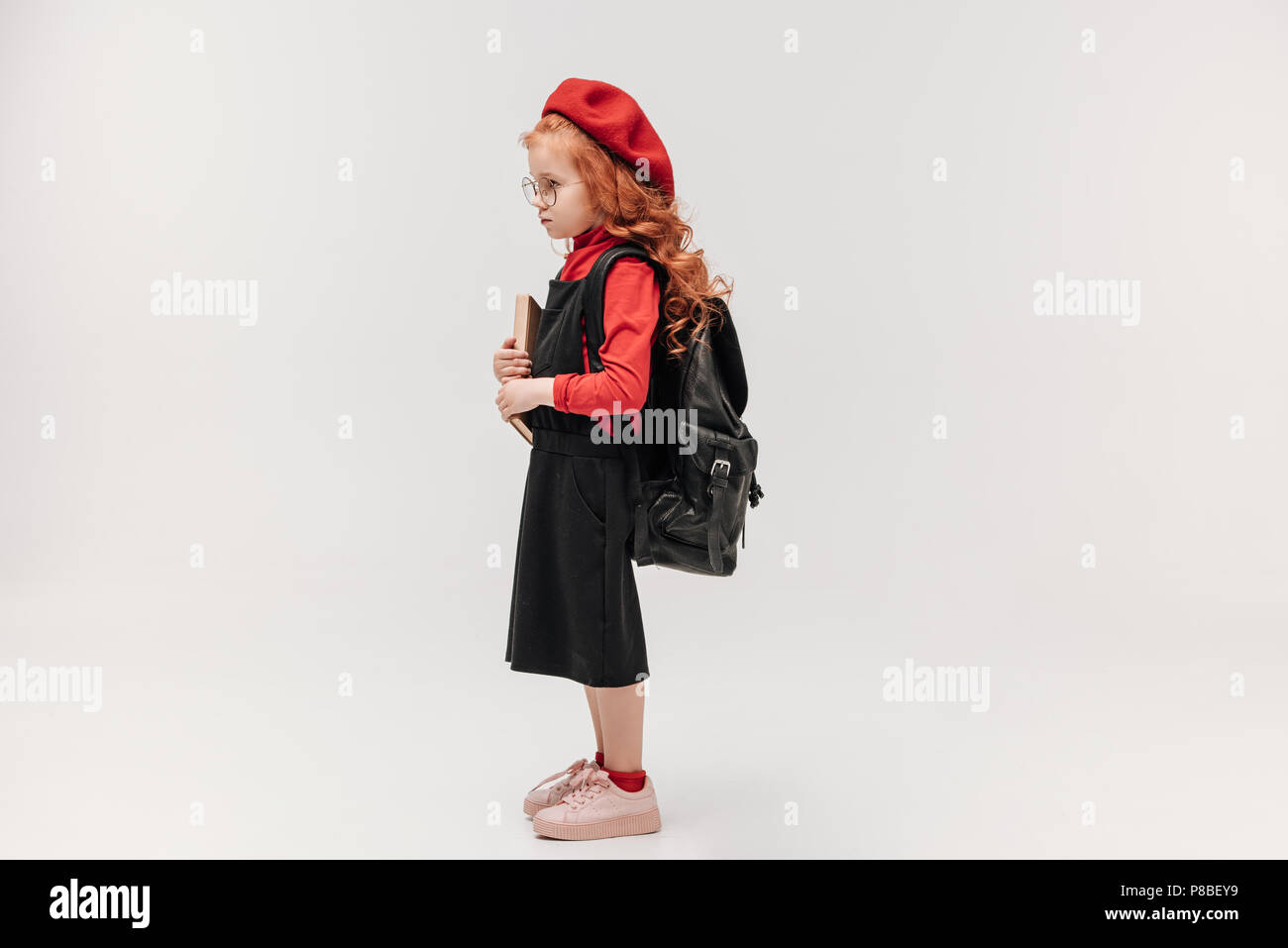 ad0f424d71 side view of adorable little schoolgirl in red beret with book and backpack  isolated on grey
