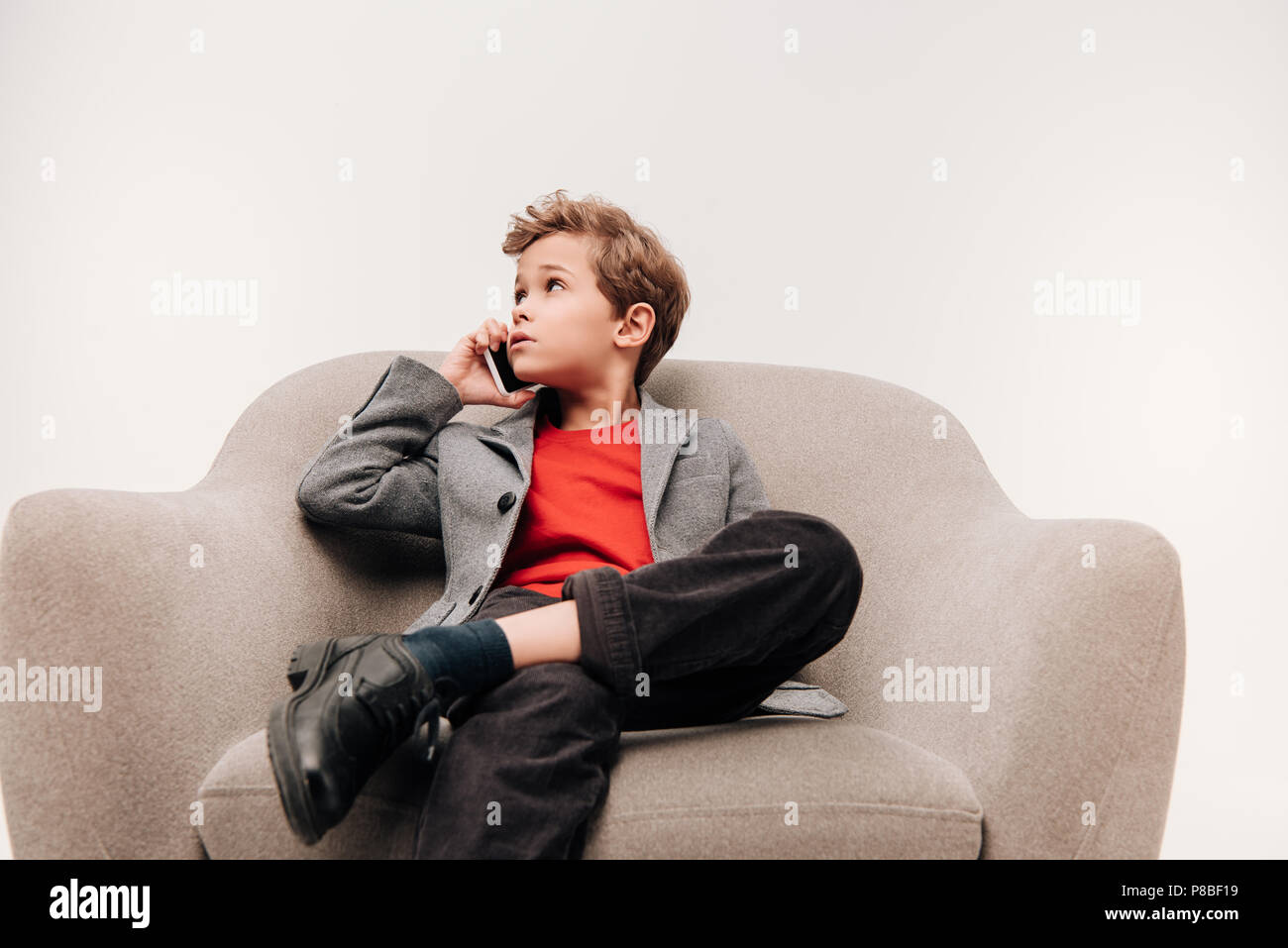 stylish little boy talking by phone while sitting in comfy armchair isolated on grey - Stock Image