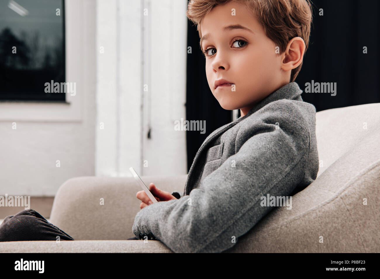 stylish little boy sitting in comfy armchair and using smartphone - Stock Image