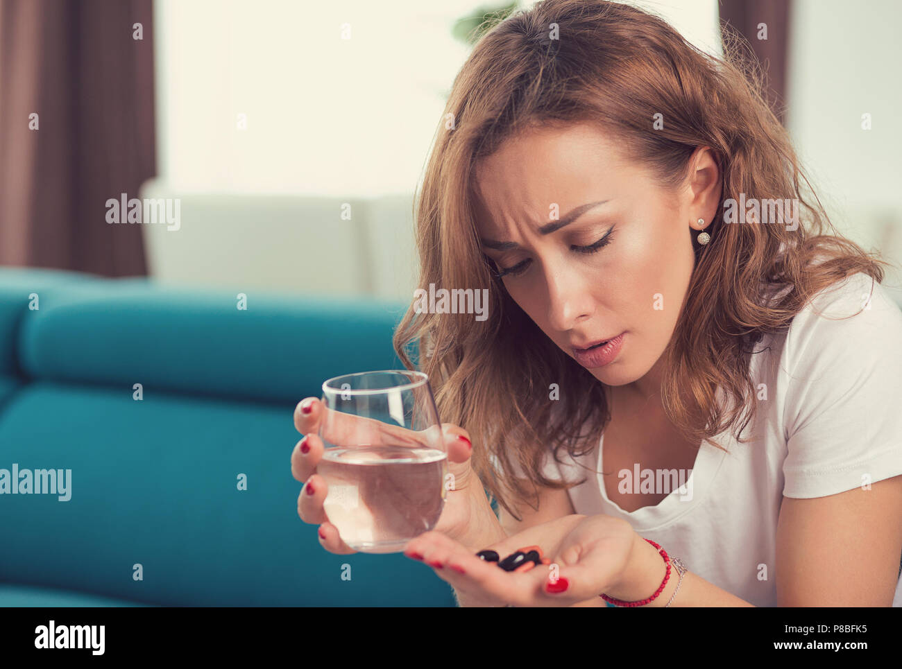stressed depressed attractive young woman with painkiller pills and glass of water sitting on a sofa in her apartment - Stock Image