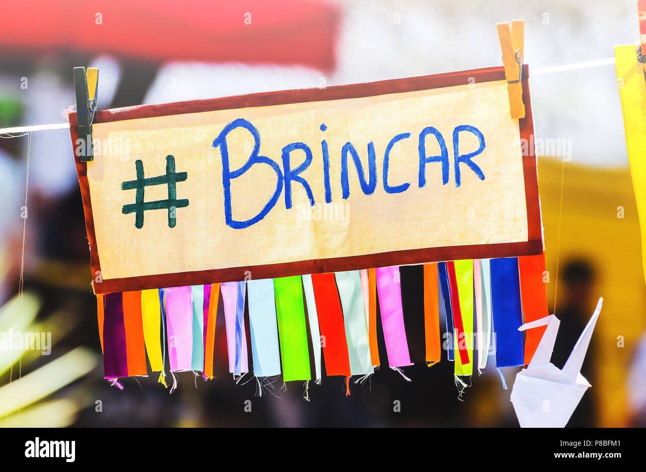 Colorful board with the message 'play' written in Brazilian portuguese suspended by a rope clamped with clips. Brincar message, #brincar, hashtag brin Stock Photo