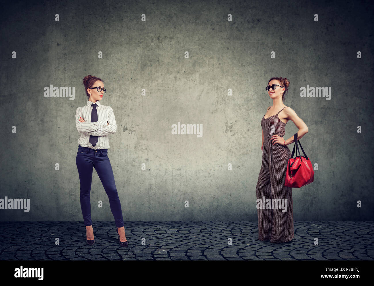 Young woman in two different outfits showing informal and formal clothes for housewife and businesswoman on gray background - Stock Image