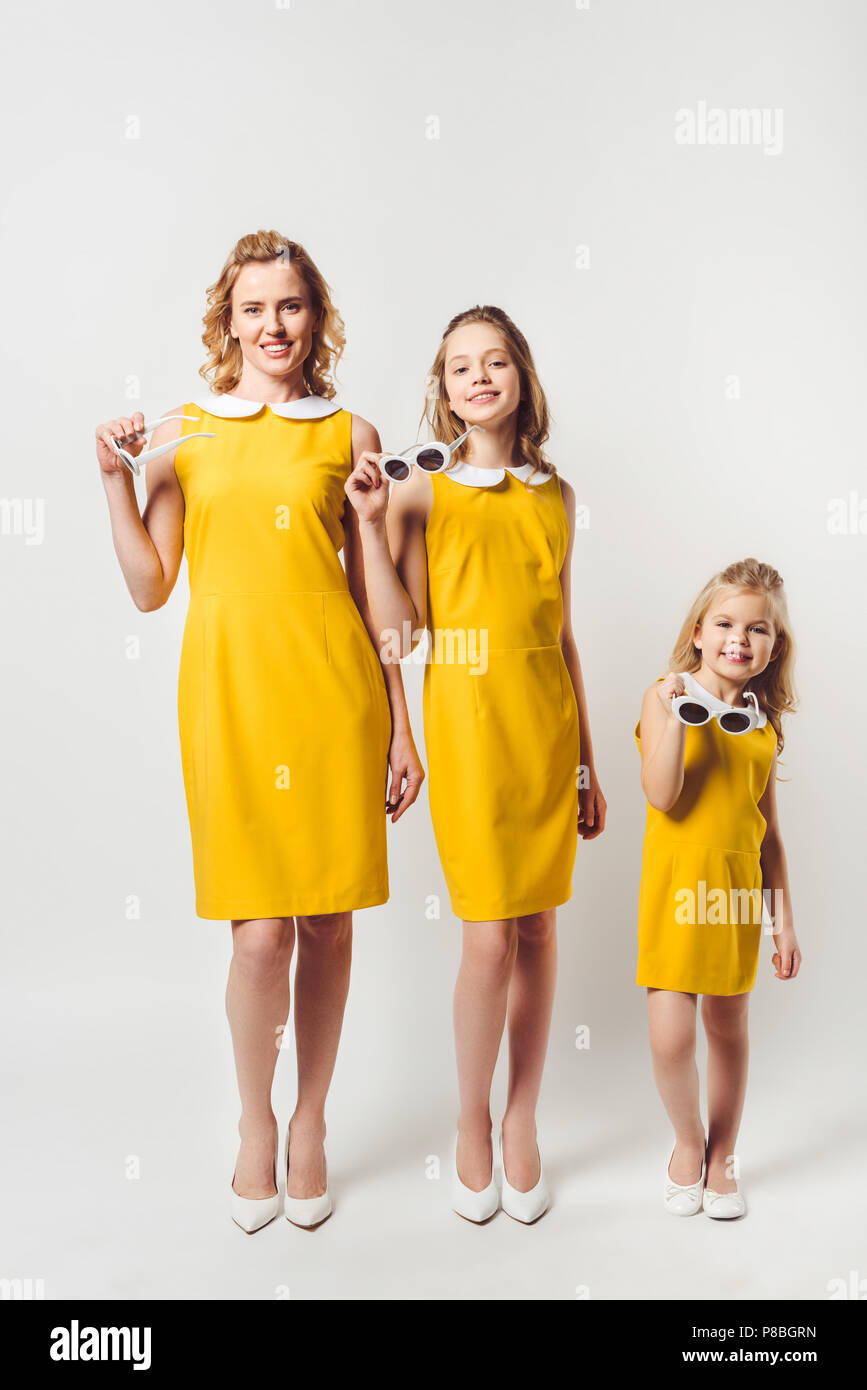 happy mother and daughters in similar retro style yellow dresses looking at  camera on white ca49dfd2d
