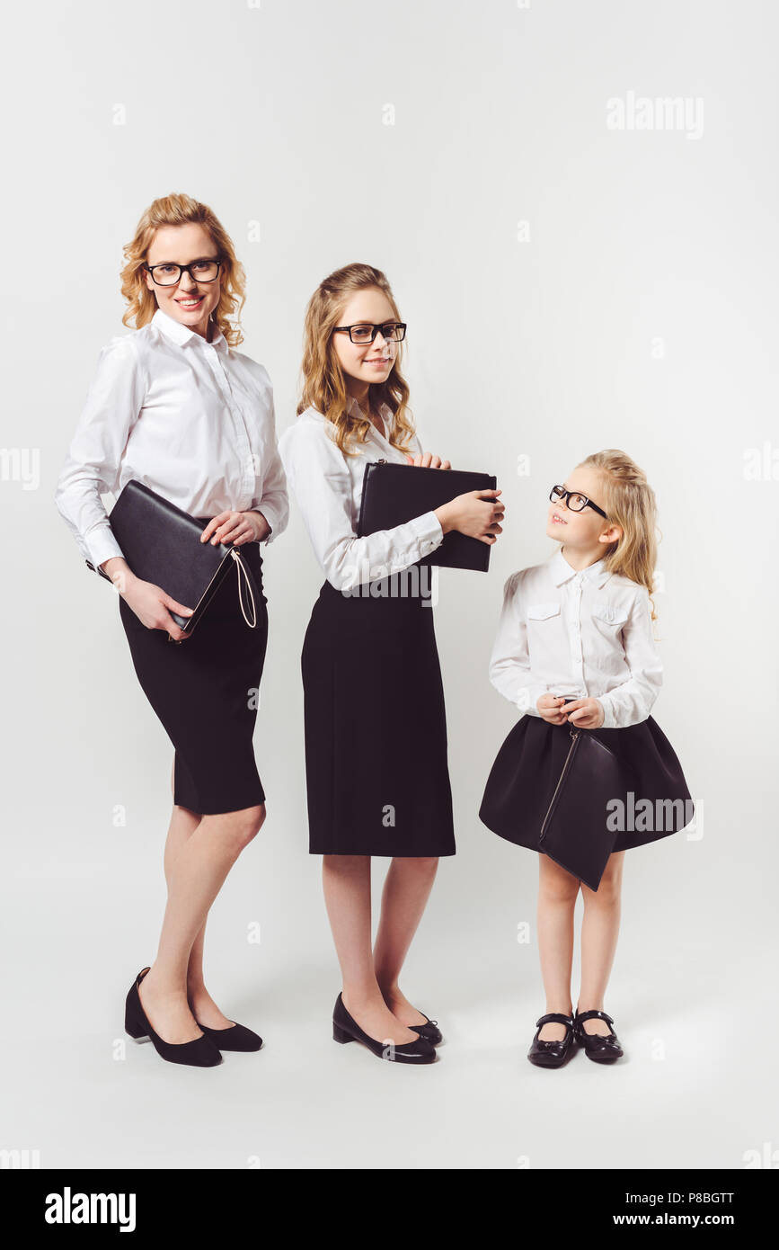 mother and daughters in similar businesswomen costumes with clutches on white - Stock Image