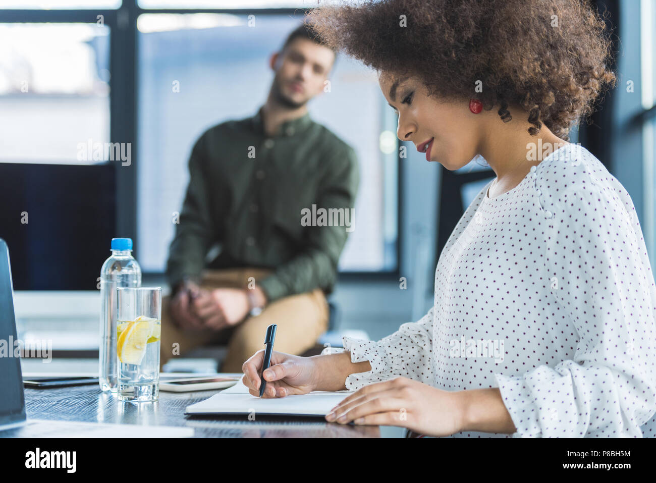 side view of african american businesswoman writing something in office - Stock Image