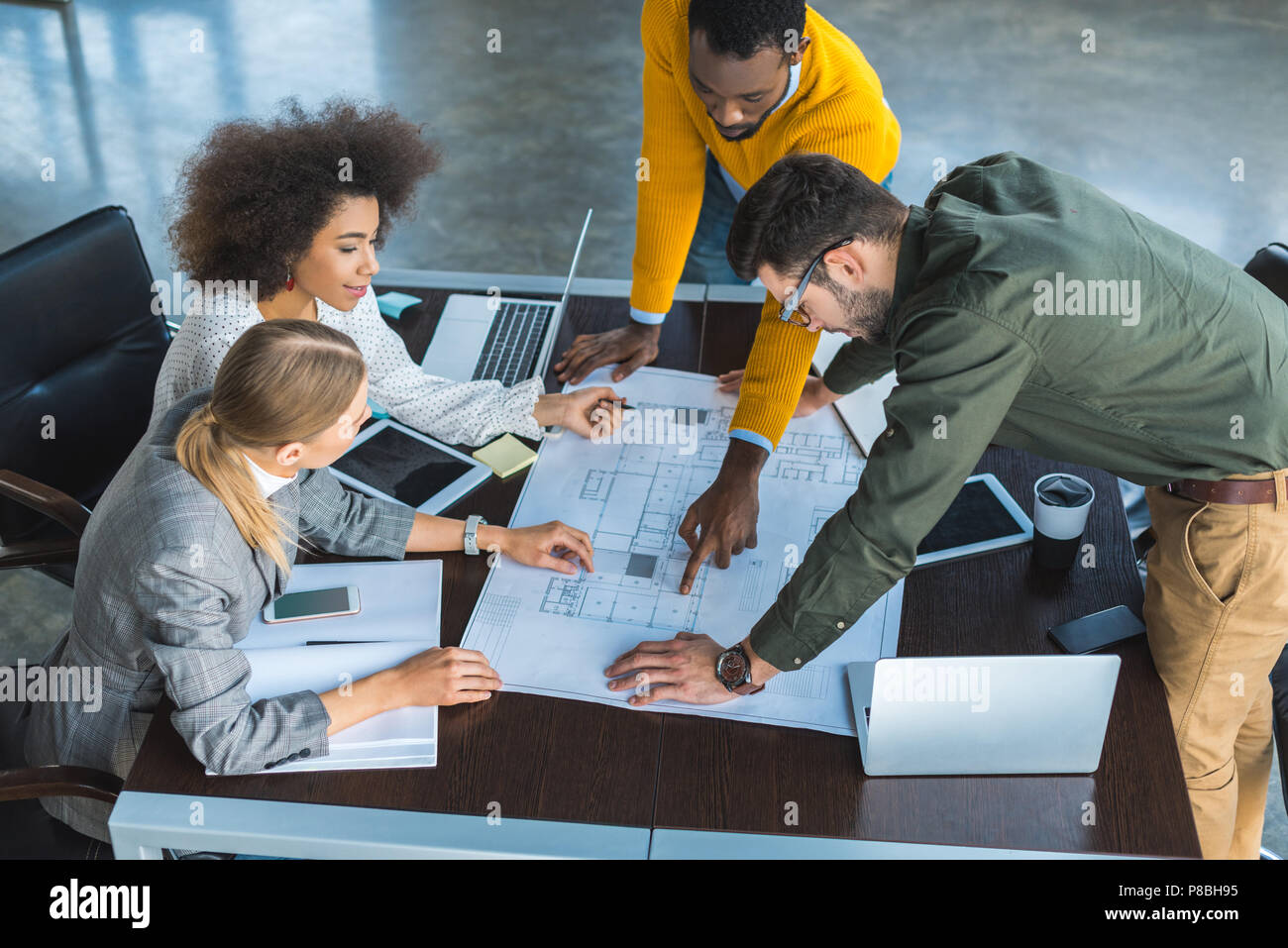 high angle view of african american businessman pointing on something at blueprint in office - Stock Image