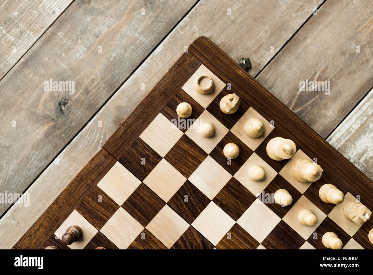 Cropped view of chess baord with chess pieces on rustic wooden surface - Stock Image