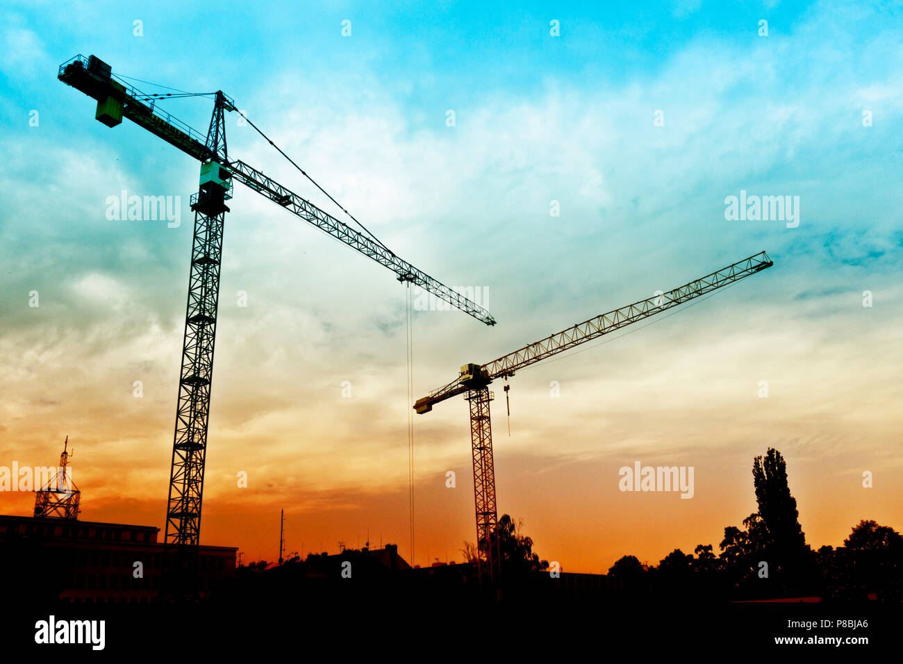 tower cranes in silhouette at a construction site - Stock Image