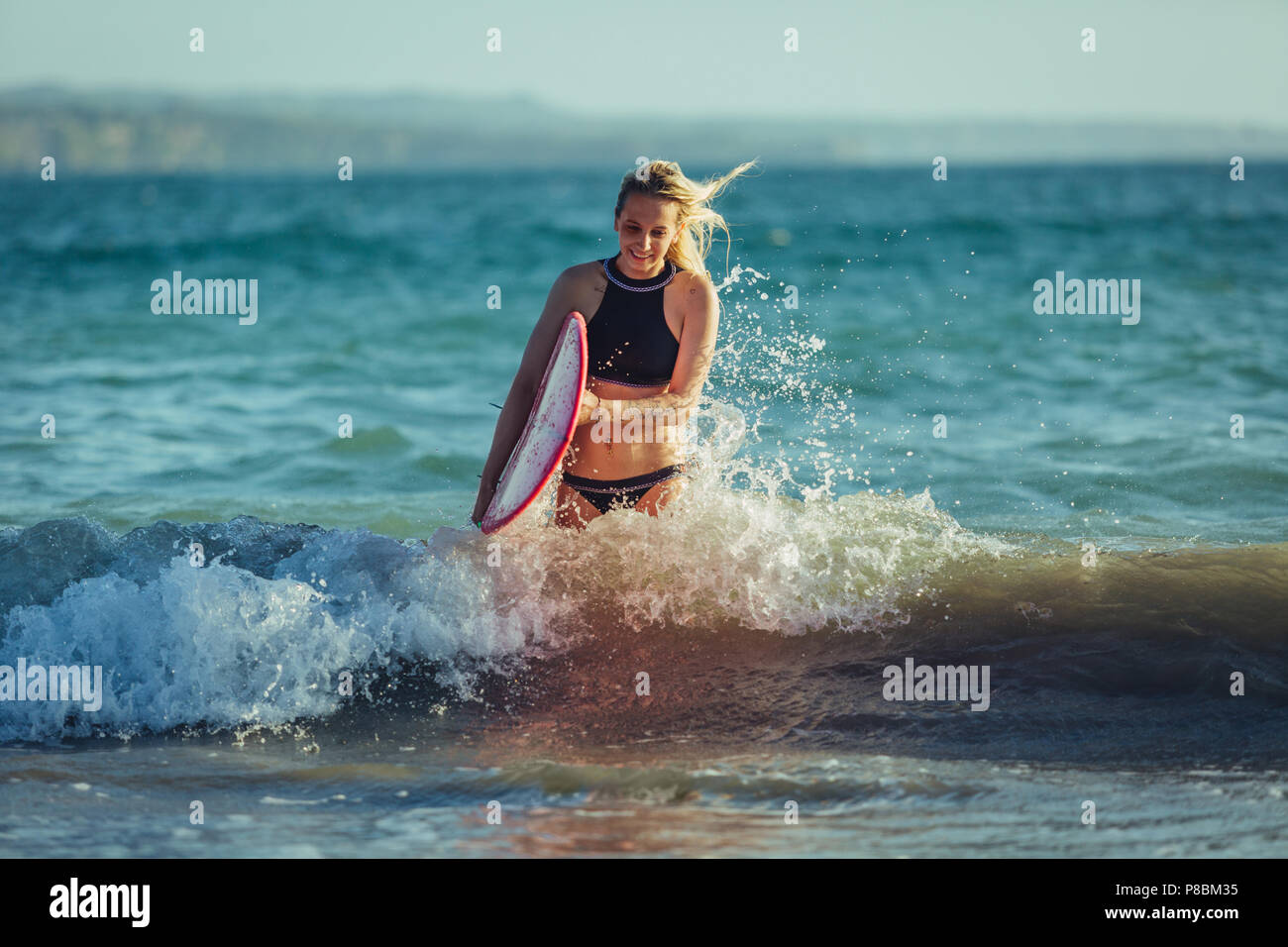 blonde female surfer with surfboard in water - Stock Image