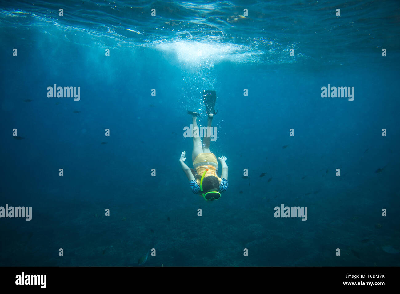 underwater photo of woman in fins, diving mask and snorkel diving alone in ocean Stock Photo