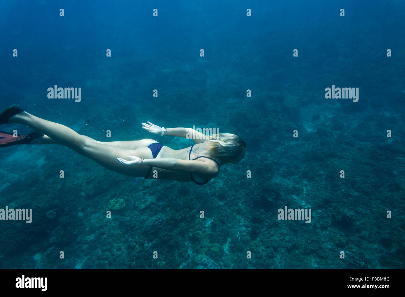 side view of woman in bikini and fins diving in ocean alone - Stock Image
