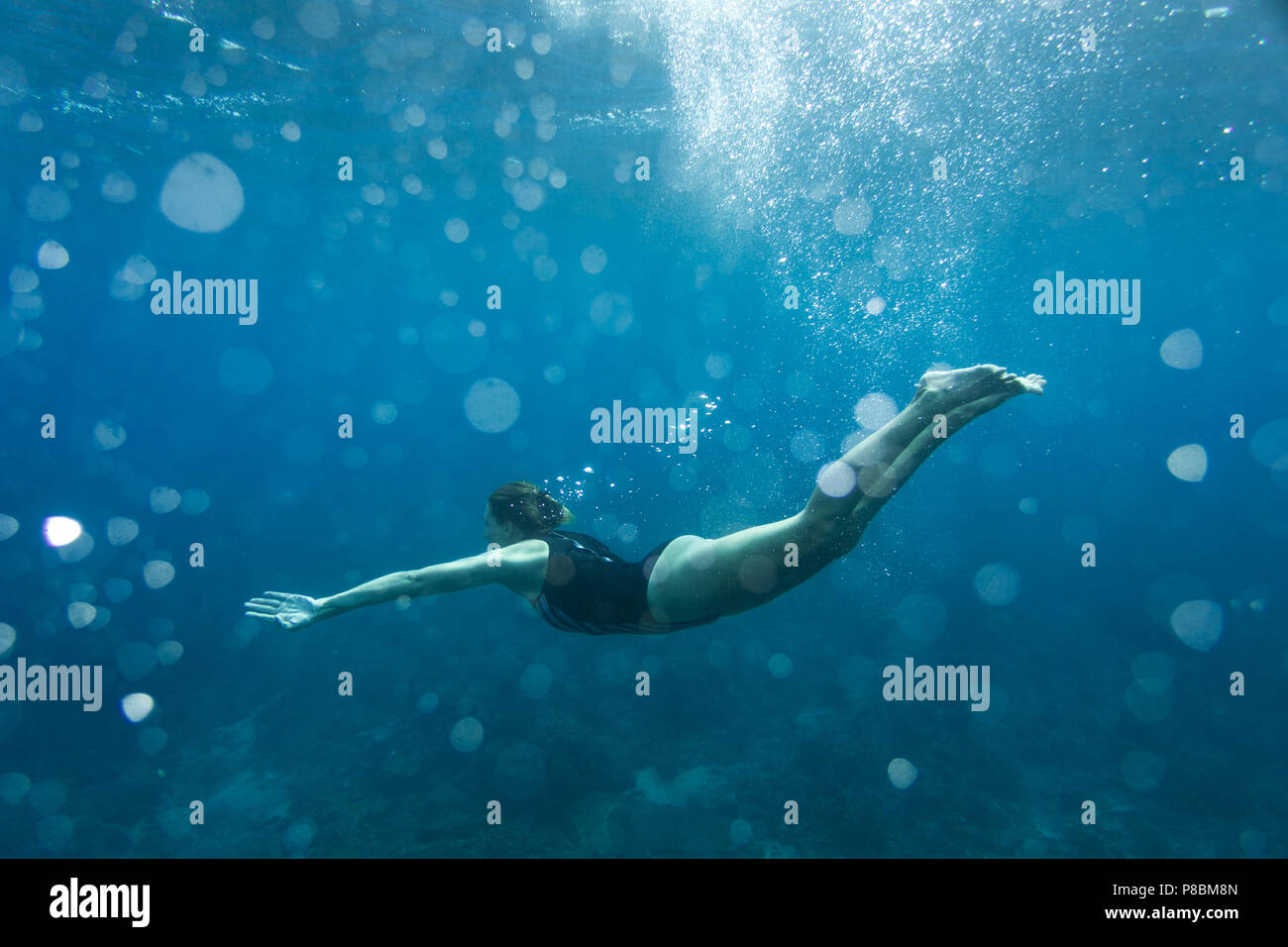 underwater photo of young woman in swimming suit diving in ocean alone Stock Photo