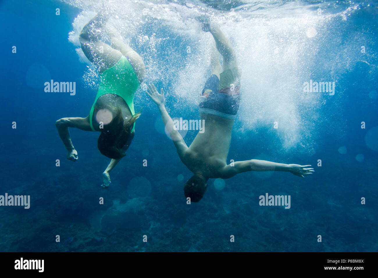 underwater photo of couple diving together in ocean Stock Photo
