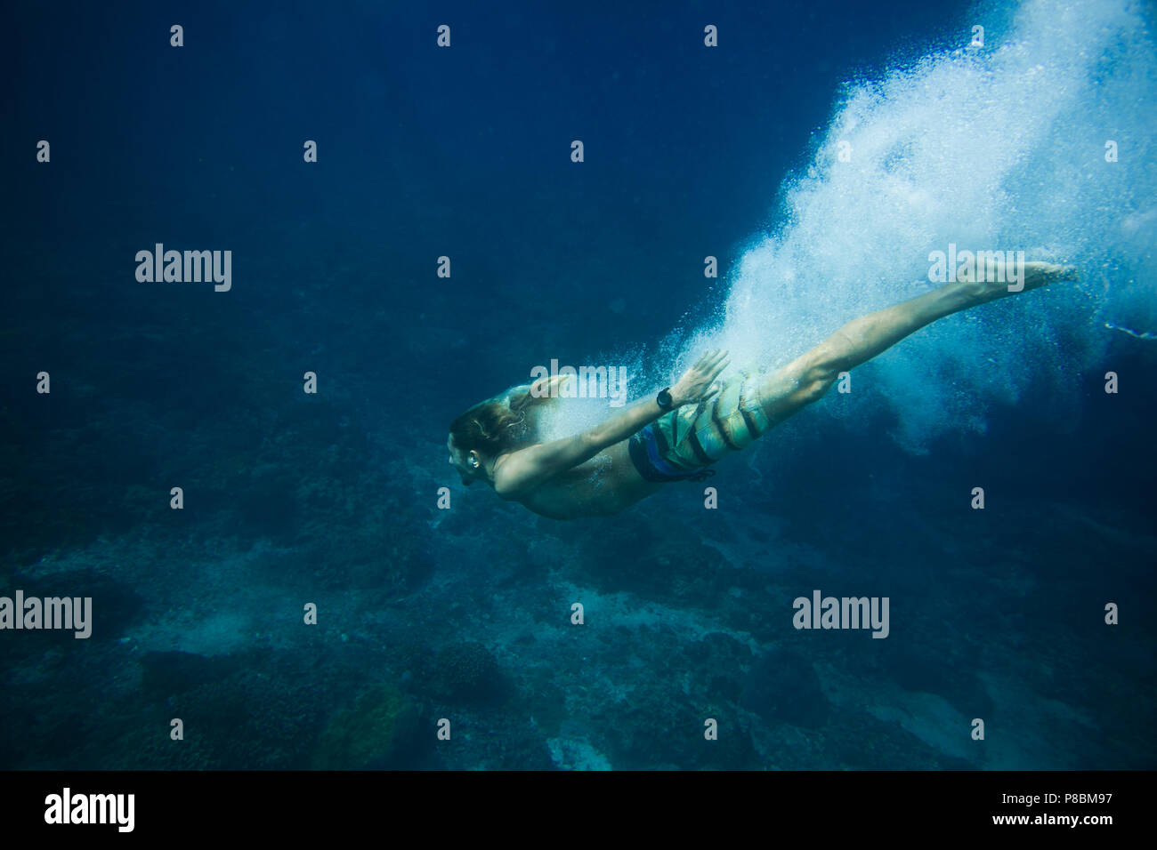 underwater pic of young man diving in ocean alone - Stock Image