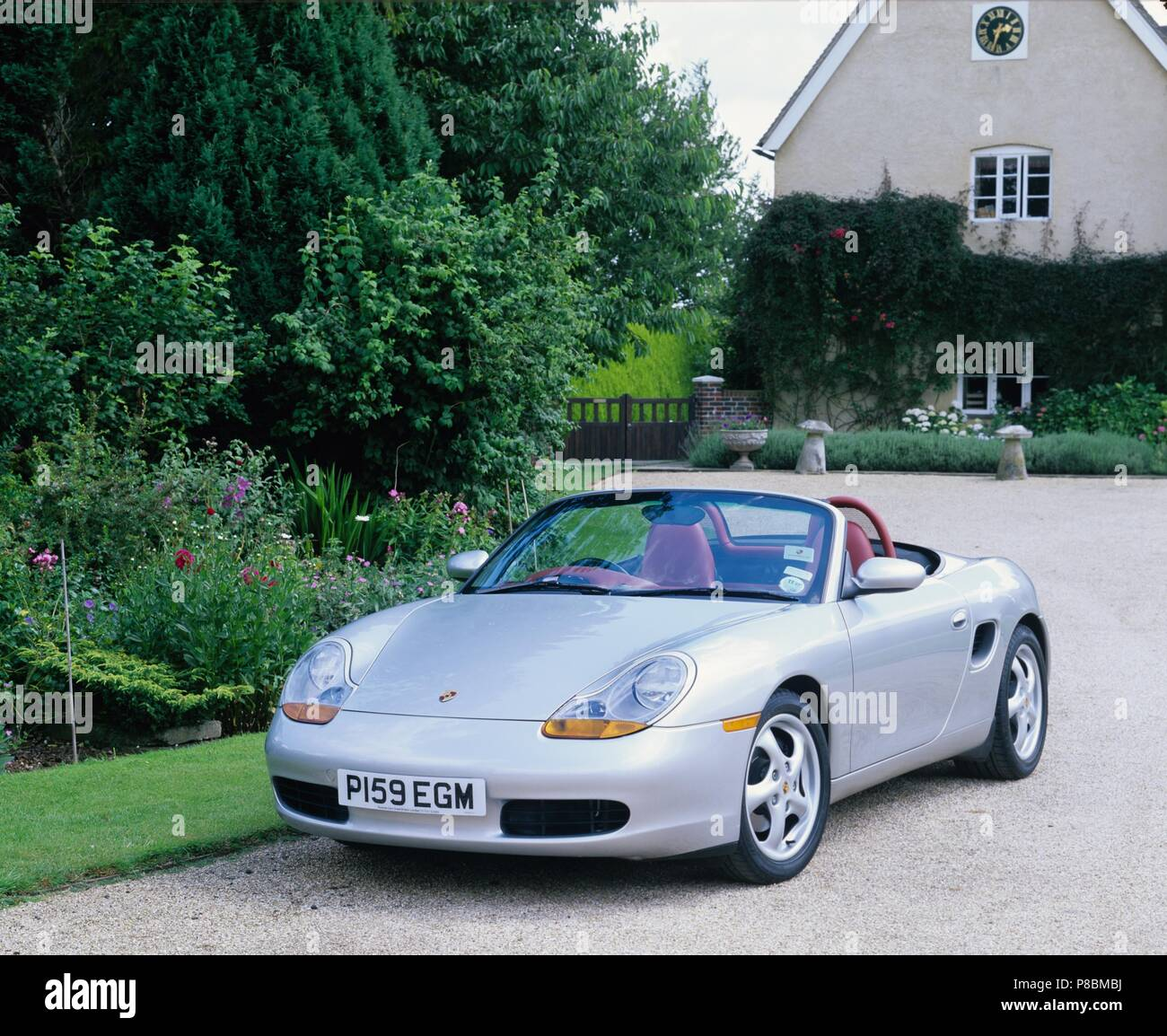 Porsche Boxster 2.5L engine - 1997 model year in silver metallic and in countryside setting showing front view with roof down - Stock Image