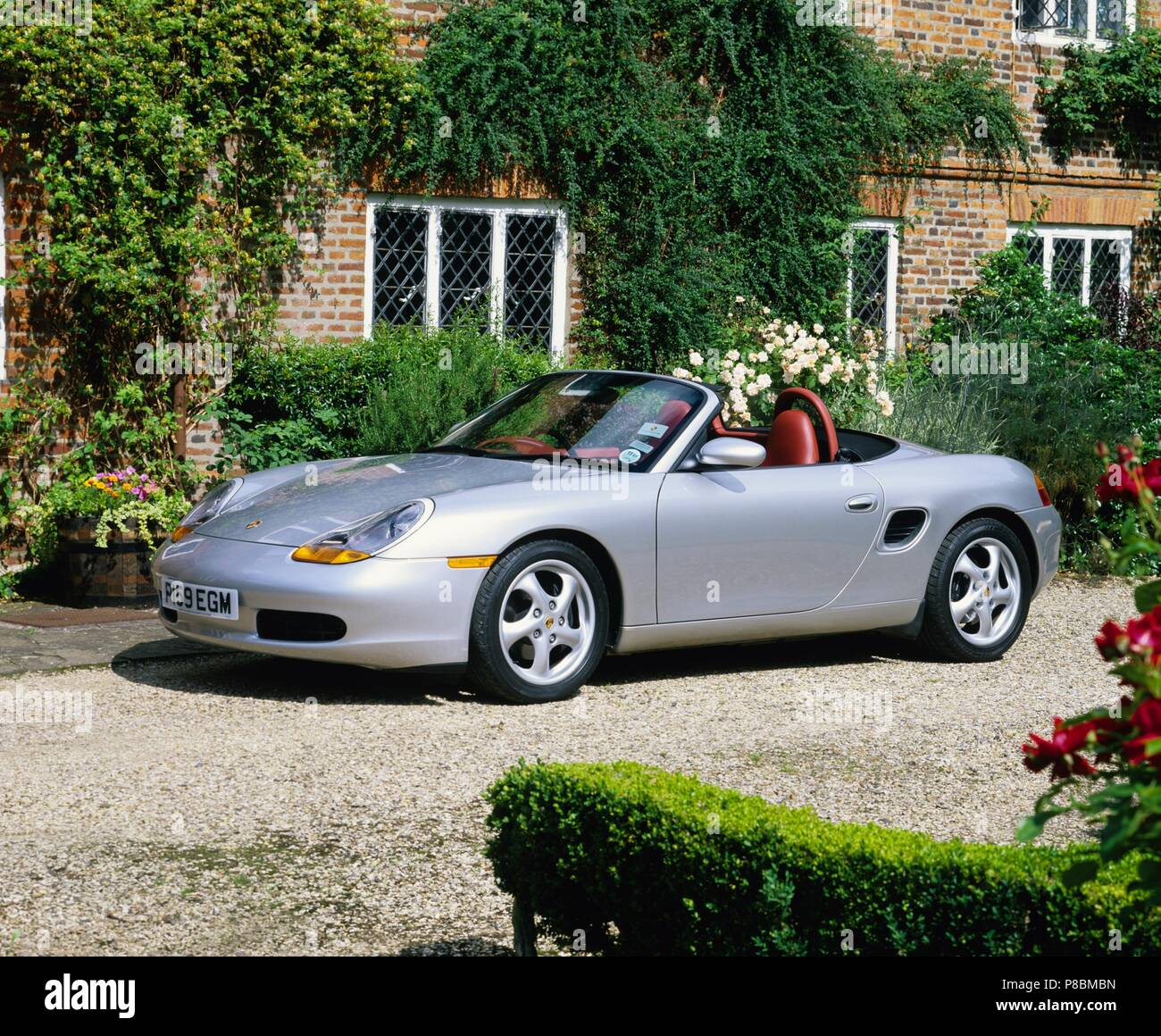 Porsche Boxster 2.5L engine - 1997 model year in silver metallic and in countryside setting showing front and side view with roof down - Stock Image