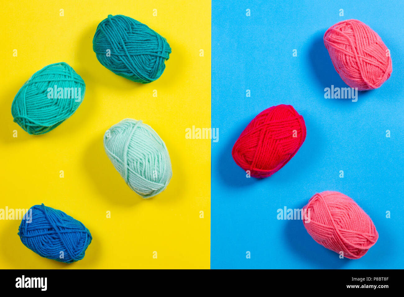 Colorful yarn for knitting on yellow and blue background. - Stock Image