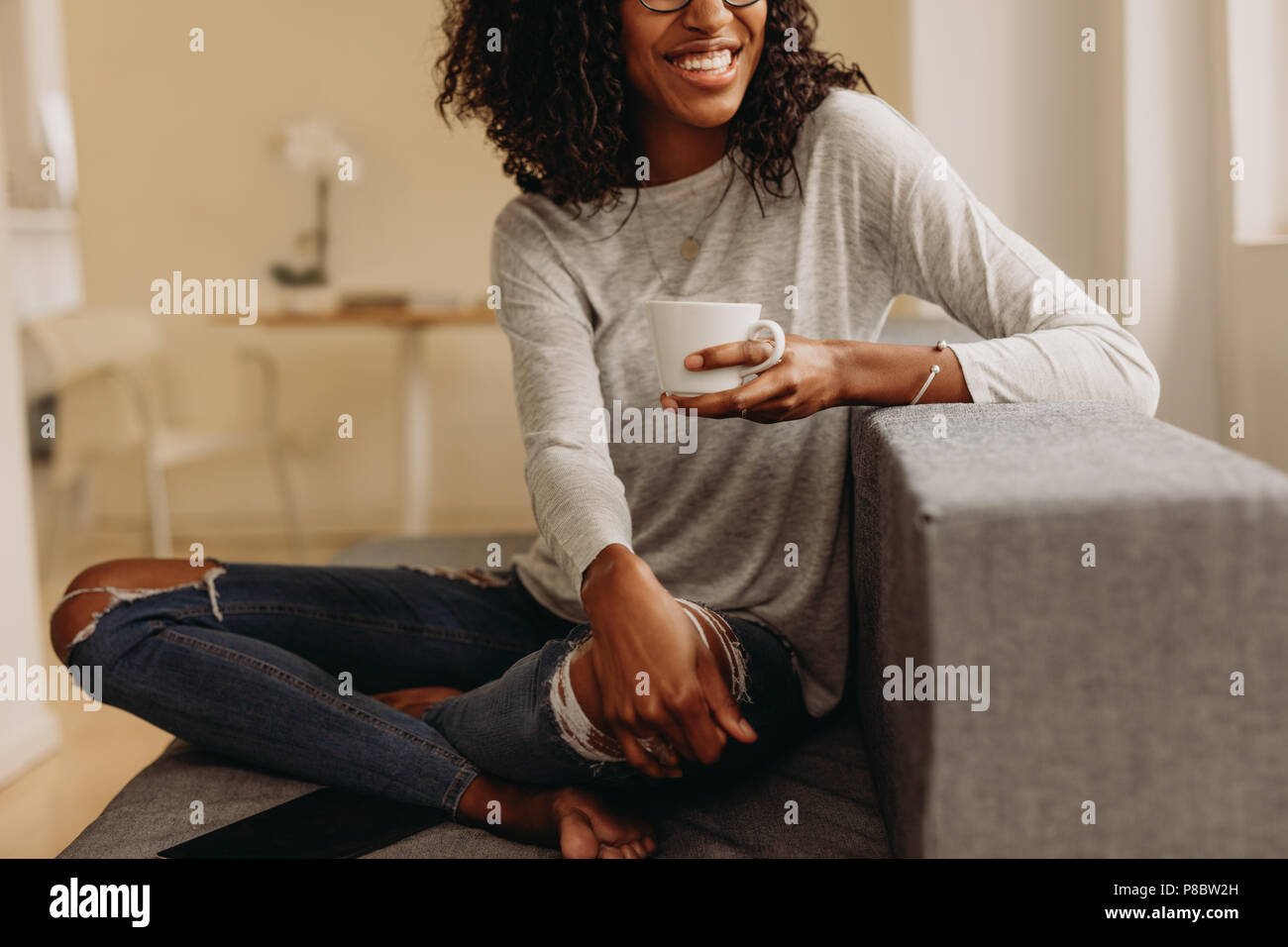 Smiling woman in fashionable torn jeans holding a coffee cup relaxing at home. Woman sitting with legs crossed on sofa at home drinking coffee and loo - Stock Image