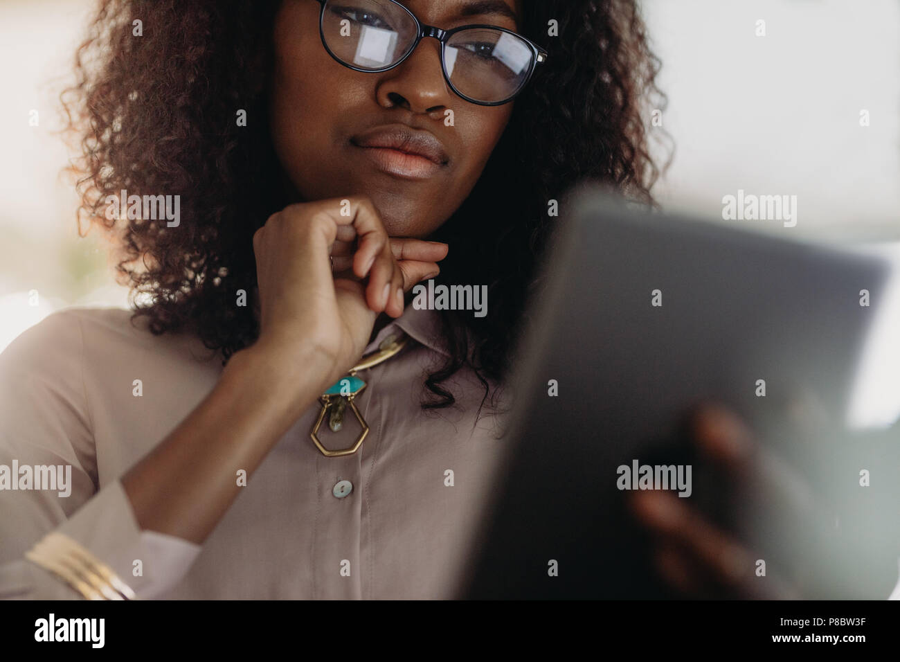 Close up of a curly haired businesswoman in spectacles looking at tablet pc with hand on chin. Low angle view of woman entrepreneur in formal attire l - Stock Image