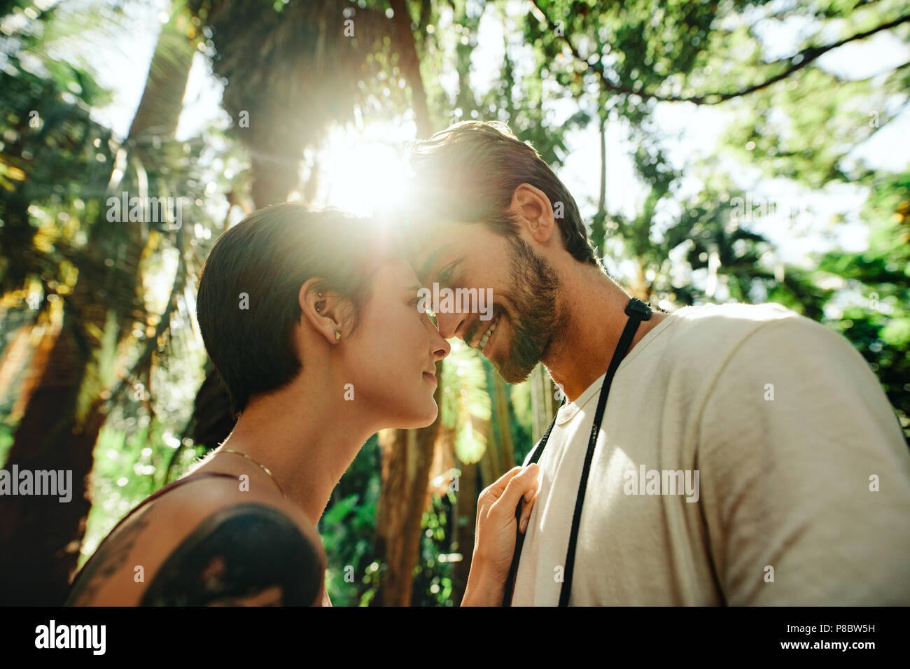 Man and woman standing close touching their foreheads in a park with sun in the background. Tourist couple in a happy and romantic mood while explorin - Stock Image