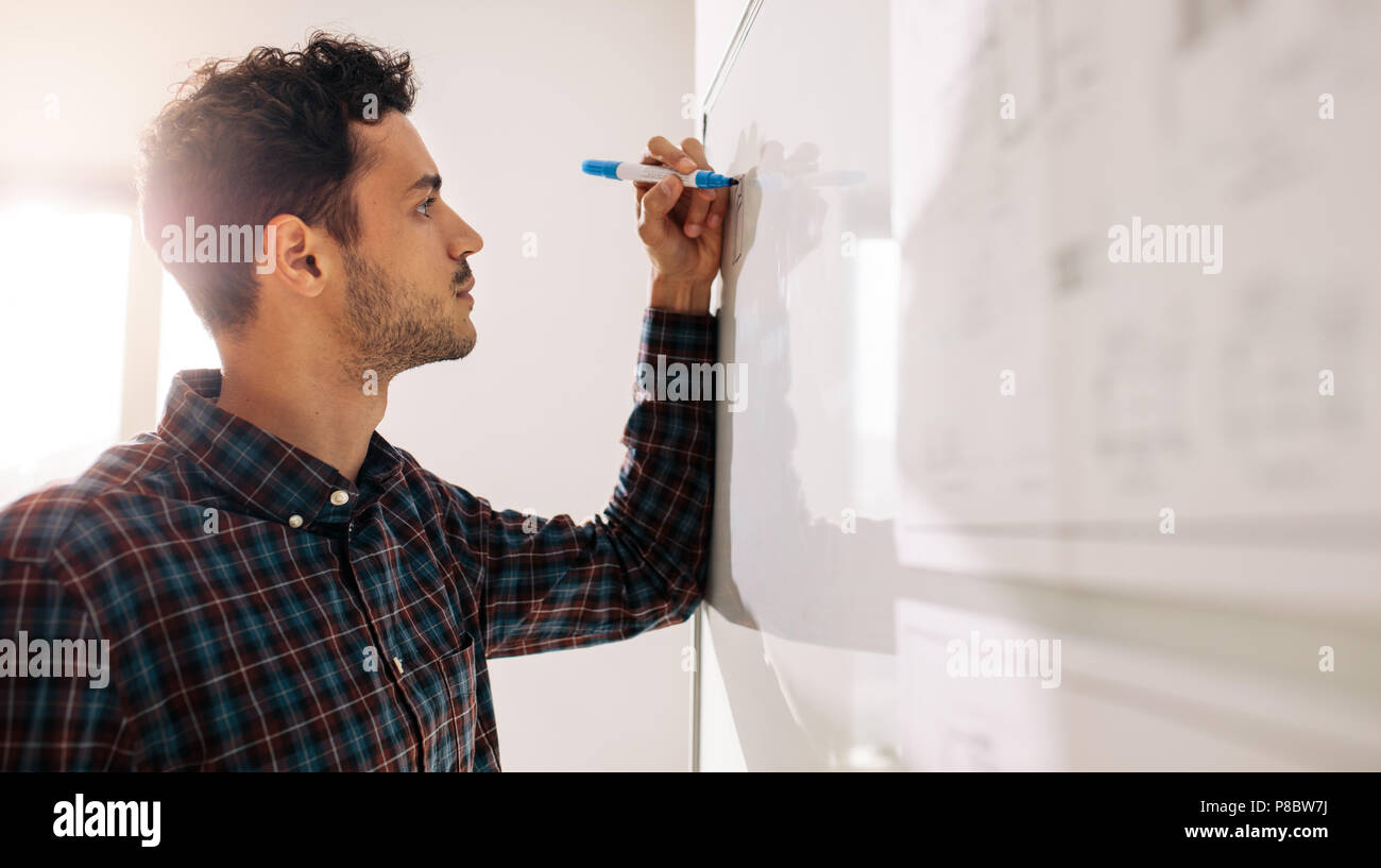 Businessman writing on a whiteboard using a marker pen. Entrepreneur discussing business ideas and plans on a board. - Stock Image