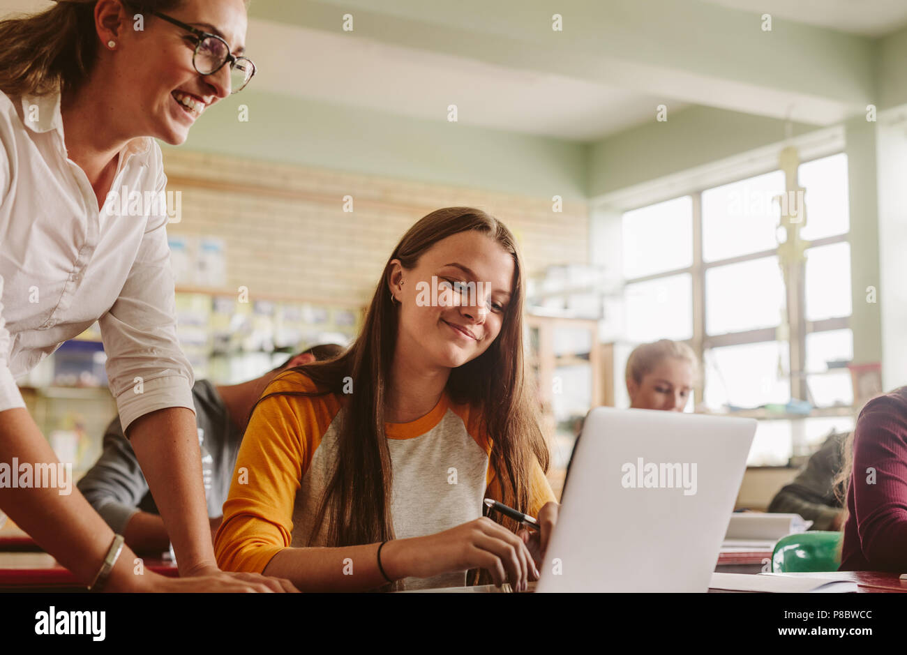 Young woman studying on laptop with teacher standing by in classroom. High school teacher helping student in classroom. - Stock Image
