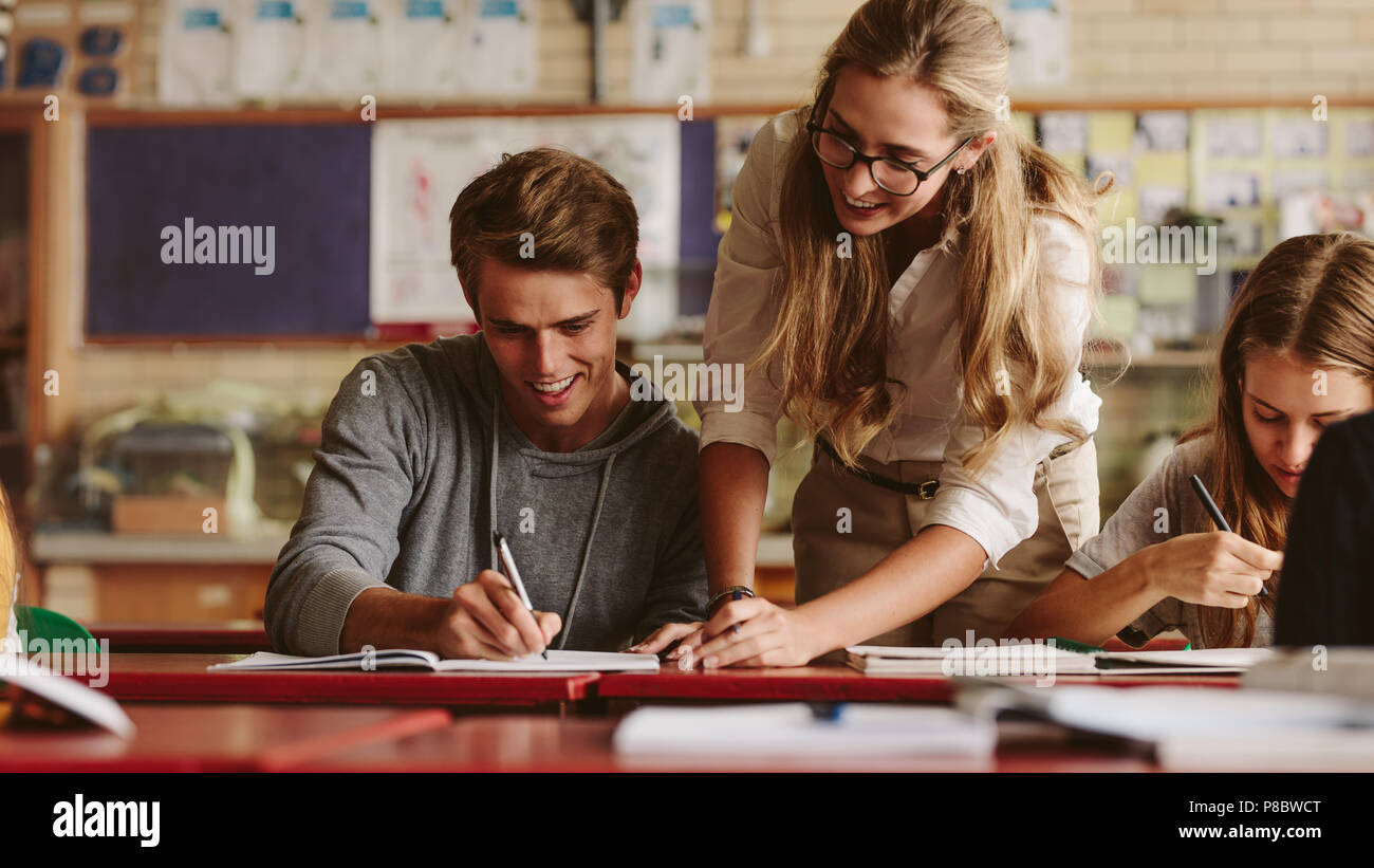 Portrait of teacher looking at her student copybook while explaining mistakes. Teacher helping student during her class. - Stock Image