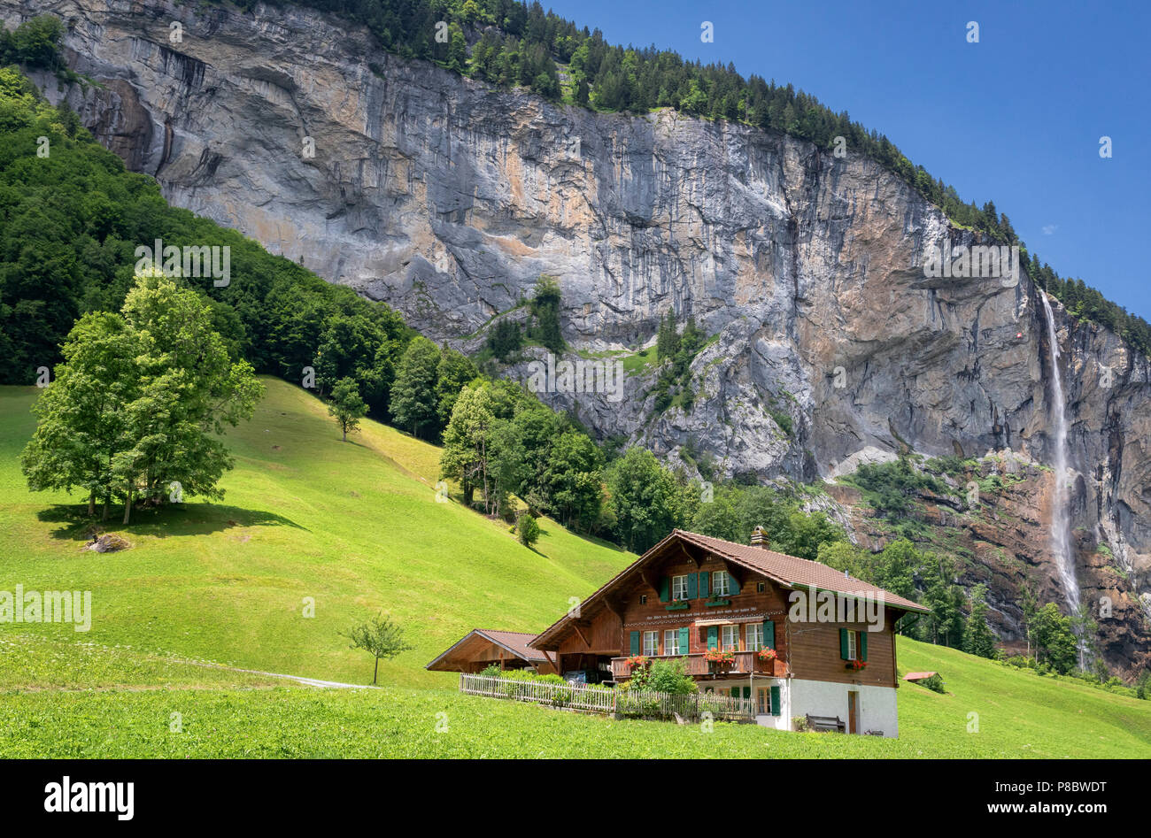 View of a farm house near Lauterbrunnen and with Staubbach Falls in the background, Interlaken-Oberhasli, Bern, Switzerland - Stock Image
