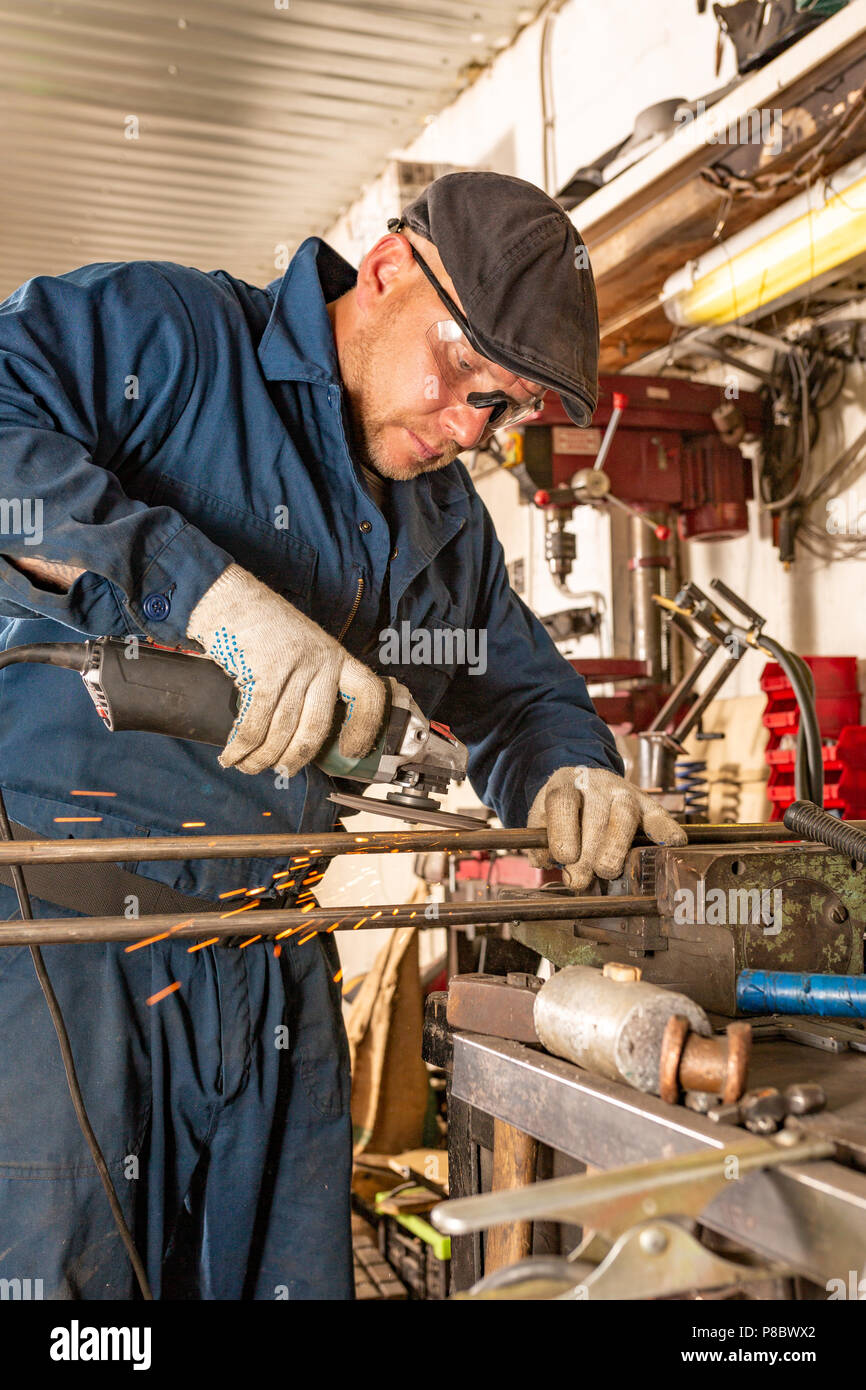 A young man welder in a blue T-shirt, goggles and construction gloves processes metal an angle grinder in the garage, in the background a lot of tools - Stock Image